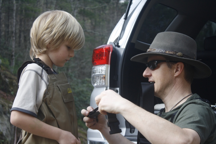 Dad teaching son about fly fishing gear